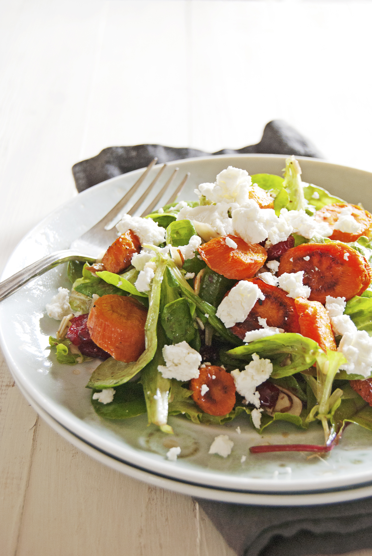 Say hello to the fall with this roasted carrot salad, featuring a balsamic vinaigrette, greens, and crumbled goat cheese.