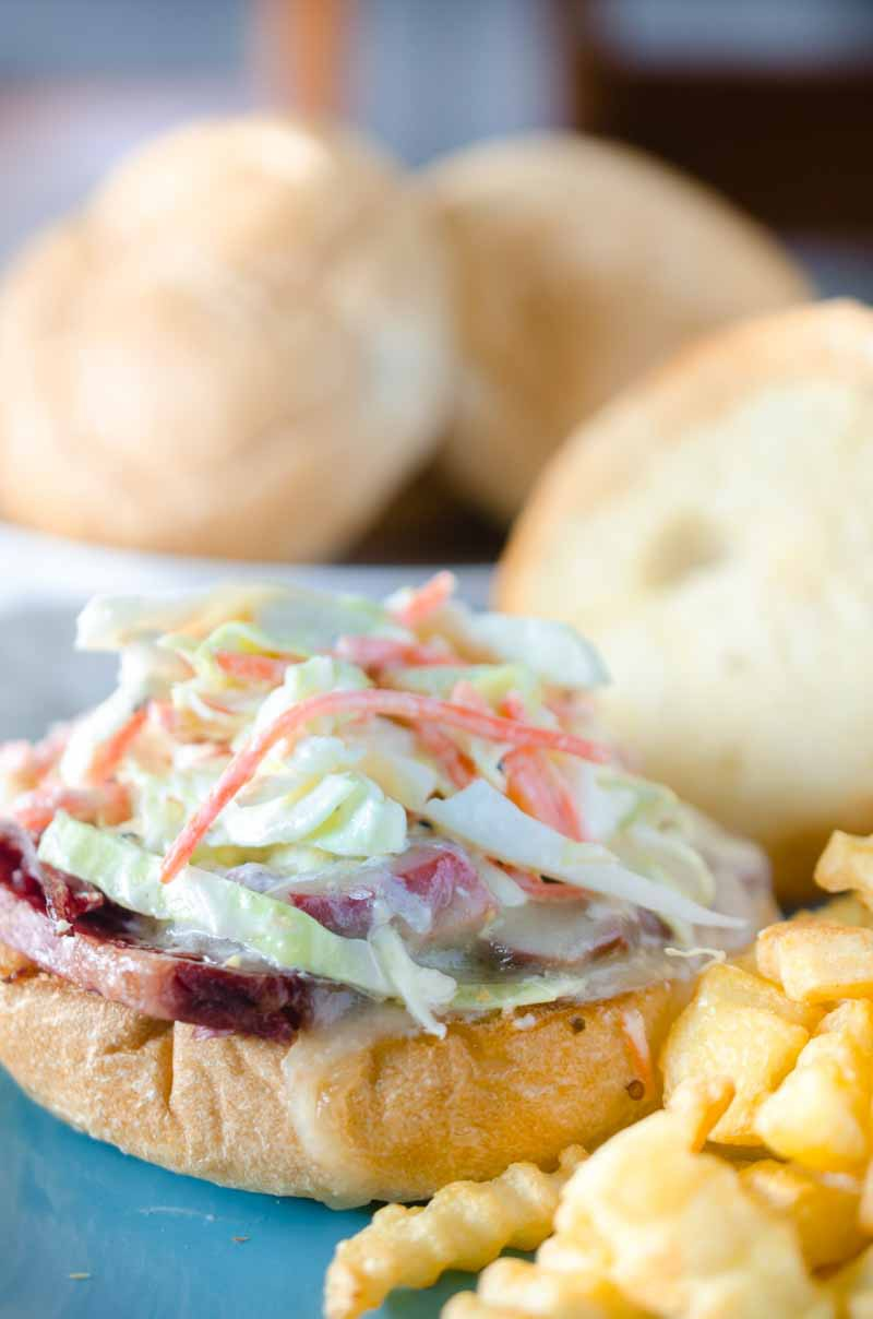Ultimate Corned Beef Sandwiches topped with melted Swiss cheese and a creamy horseradish slaw.