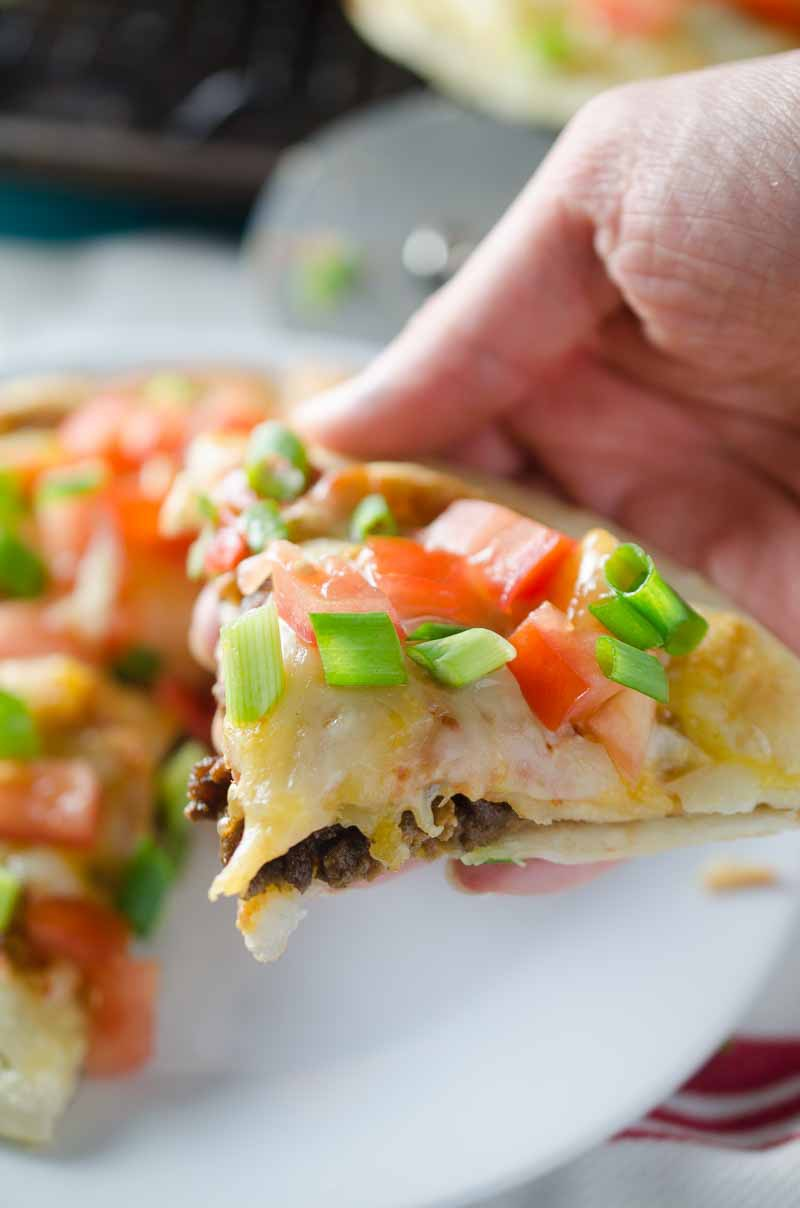 Seasoned beef & beans sandwiched between crispy tortillas, topped with cheese, spicy tomato sauce, tomatoes & green onions make this Mexican Pizza a hit!