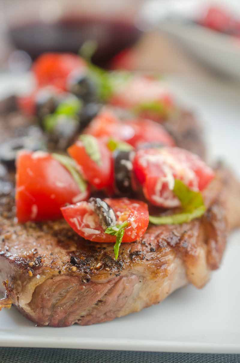 Ribeye steaks with fresh tomato tapenade are is the grilling recipe that you need this summer! Beefy goodness, topped with sweet summer tomatoes, it doesn't get much better.