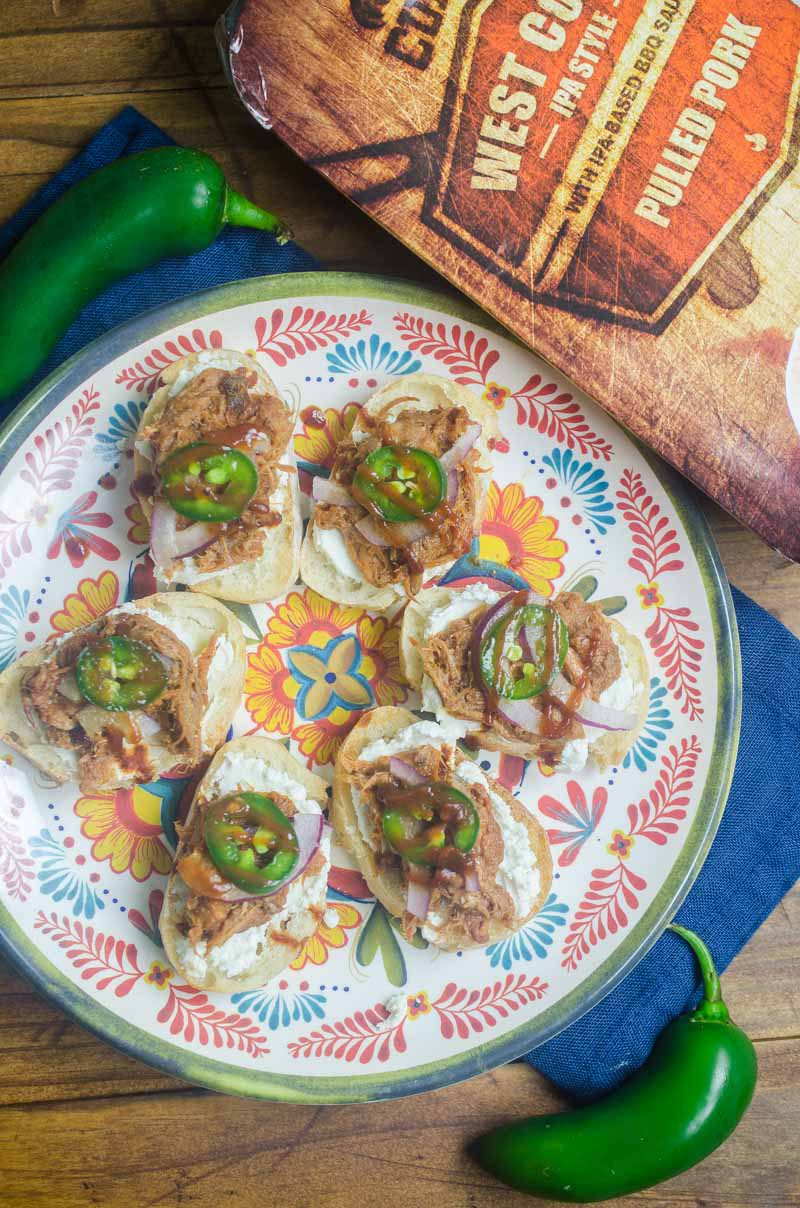 BBQ Pulled Pork Bruschetta is topped with goat cheese, Curly's RoadTrip Eats West Coast IPA Style Pulled Pork, onions, jalapenos and BBQ sauce. It's perfect for game day!