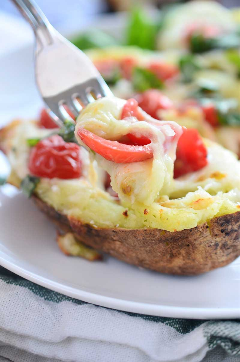 A comfort food classic gets a summer time twist with these Caprese Twice Baked Potatoes. They are loaded with pesto, mozzarella, tomatoes and fresh basil.