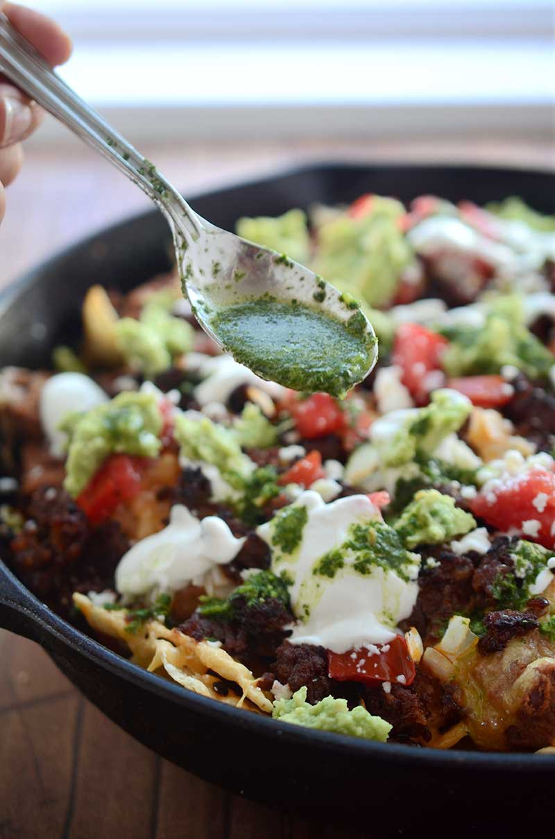 Chorizo Skillet Nachos are fully loaded with chips, refried beans, cheese, chorizo, guacamole, sour cream, onions, tomatoes and Habanero Chimichurri.