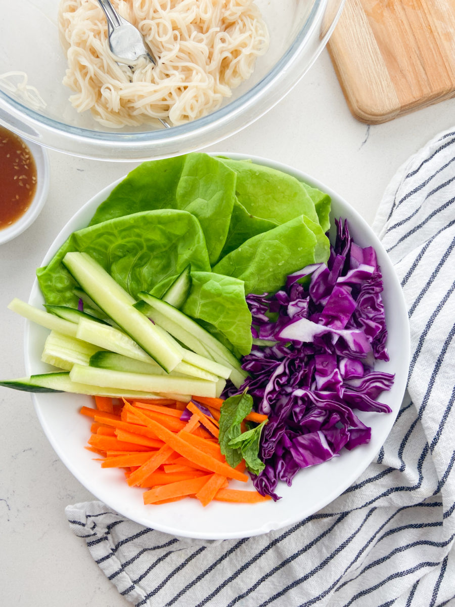 Overhead photo of fresh spring roll ingredients in a white bowl.