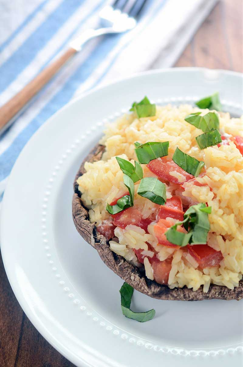 Garlic Rice Stuffed Portobello Mushrooms are stuffed with garlic rice, tomatoes and goat cheese then sprinkled with fresh basil. It is a hearty dish that is great as a side dish or a vegetarian main dish.
