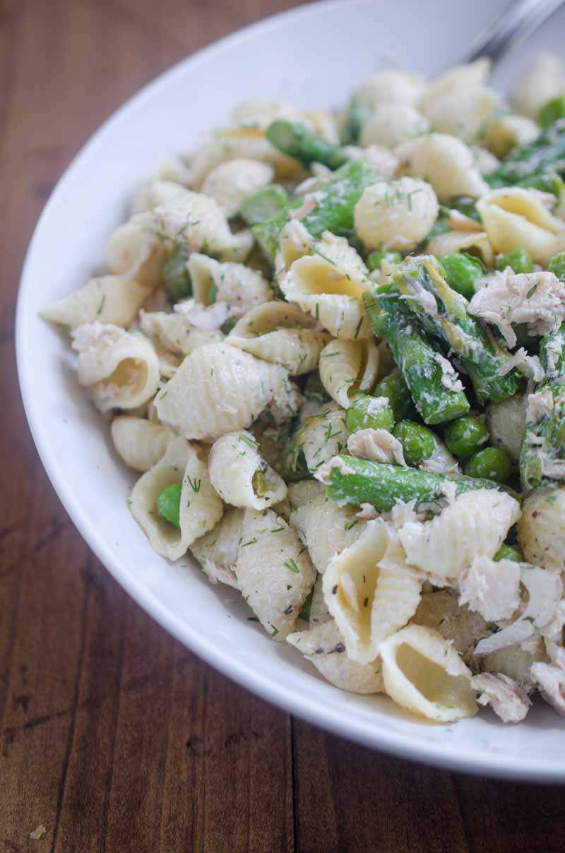 A spring take on Tuna Pasta Salad with peas and asparagus in a creamy dill dressing.