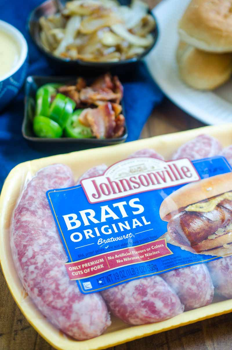 Ultimate cheesy brats are loaded with caramelized onions, cheese sauce, jalapeños and bacon. They are the perfect way to celebrate National Bratwurst day! #ad