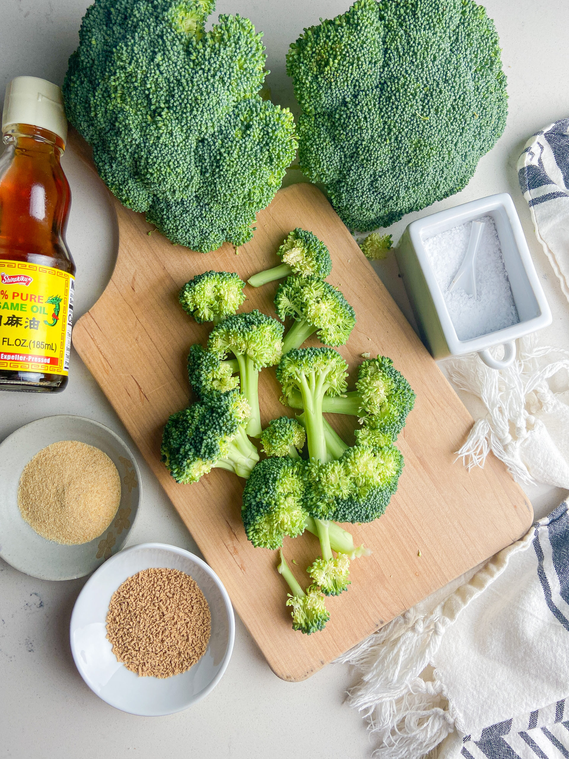 Overhead photo of ingredients needed for air fryer broccoli on a cutting board.