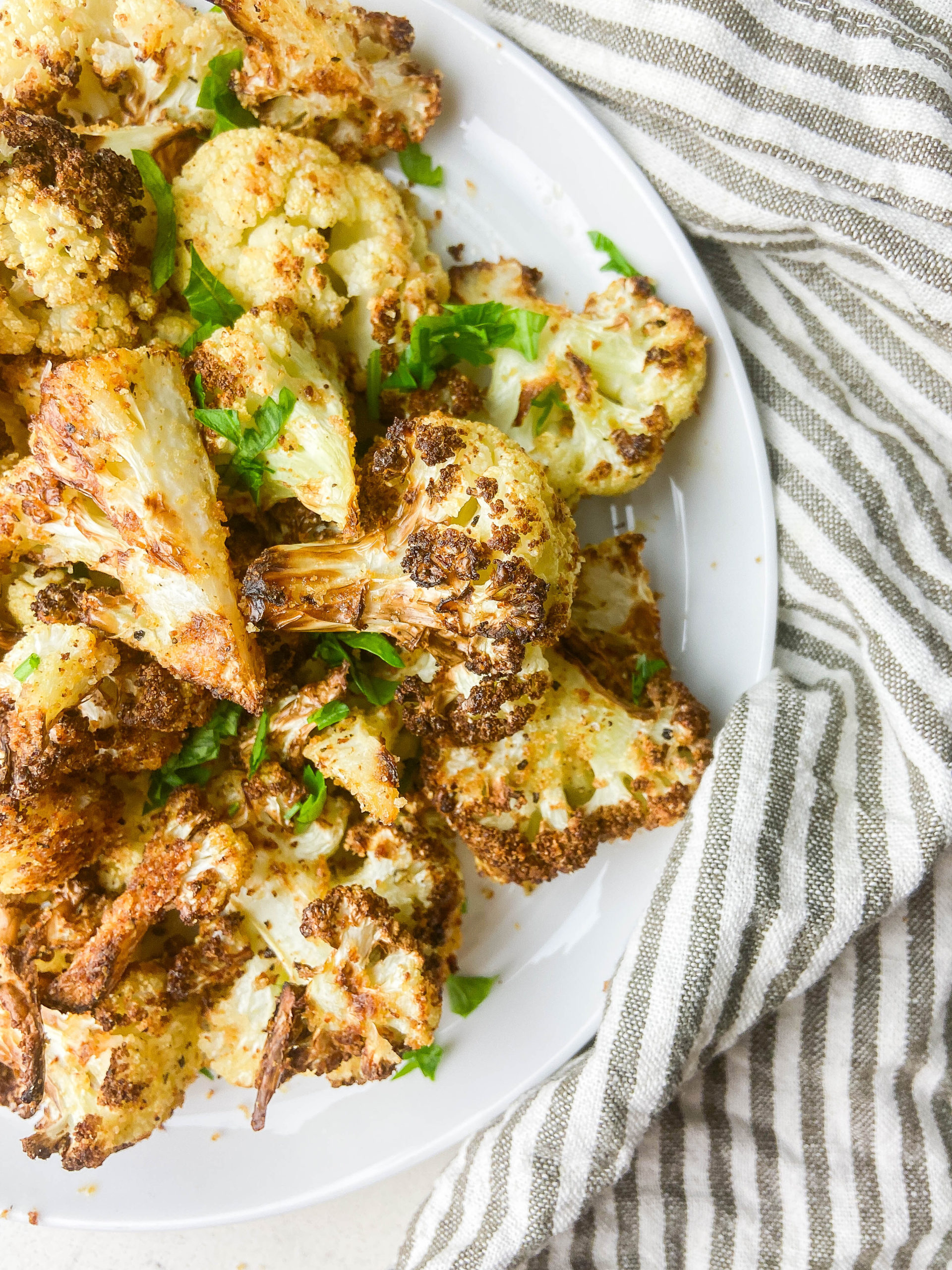 Overhead photo air fryer cauliflower on a white plate with a striped napkin.
