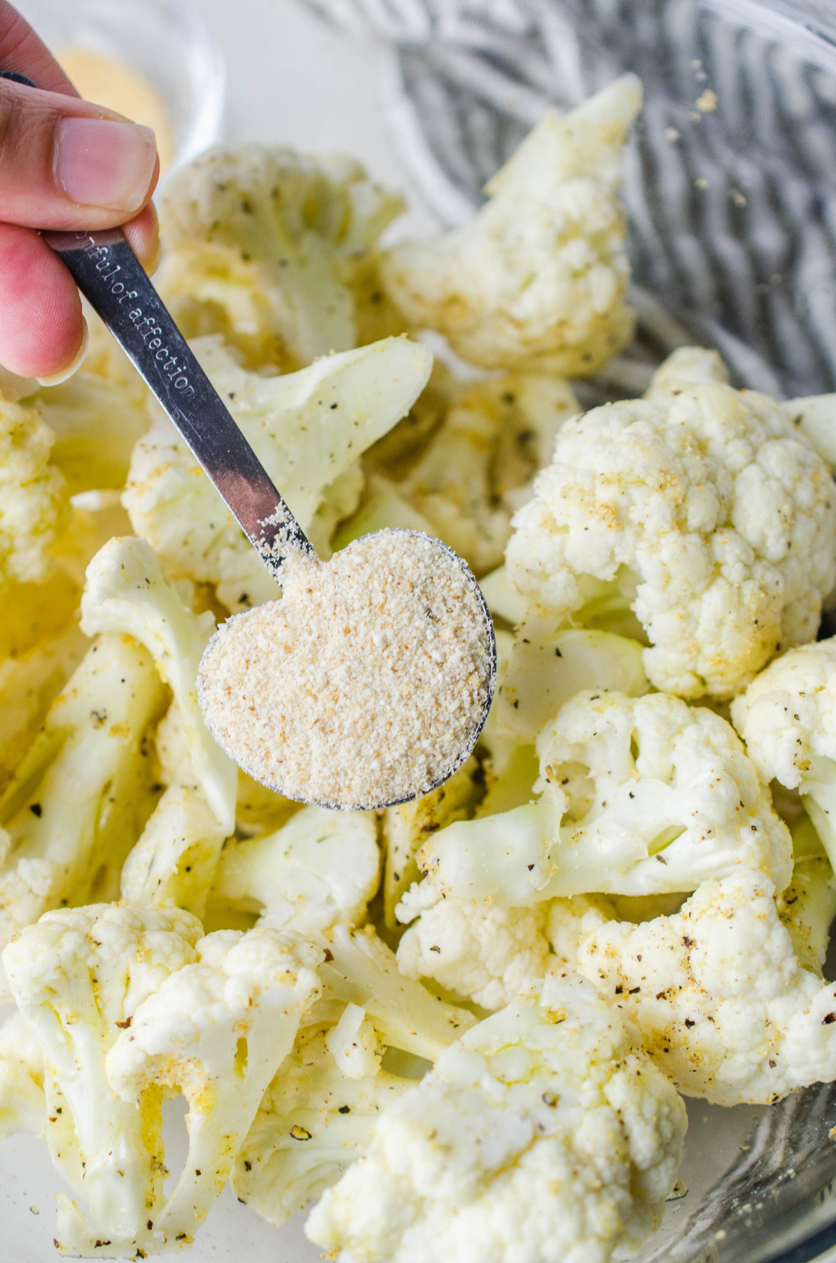 A spoonful of granulated garlic sprinkled over raw cauliflower