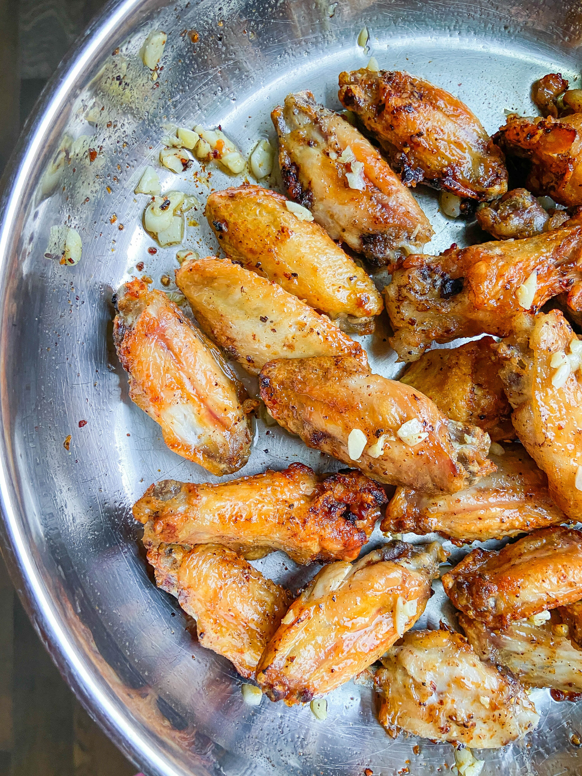 Cooked garlic wings in a frying pan.