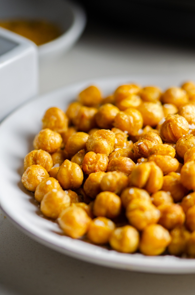 Close up side view of air fryer chickpeas on a white plate.