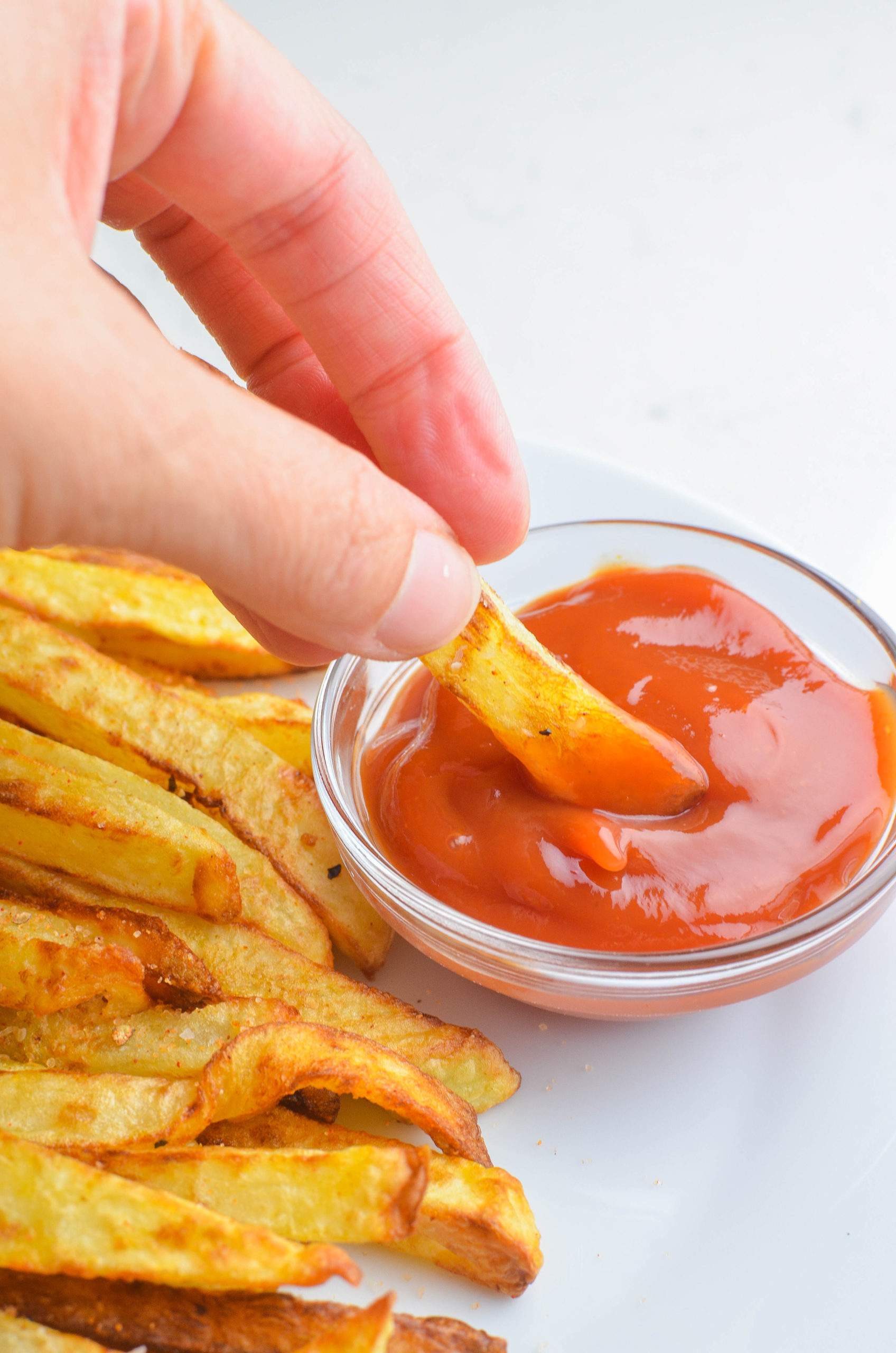 Dipping air fried french fries in ketchup