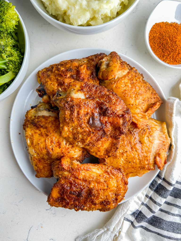 Overhead photo of air fryer chicken thighs on white plate with broccoli and mashed potatoes.