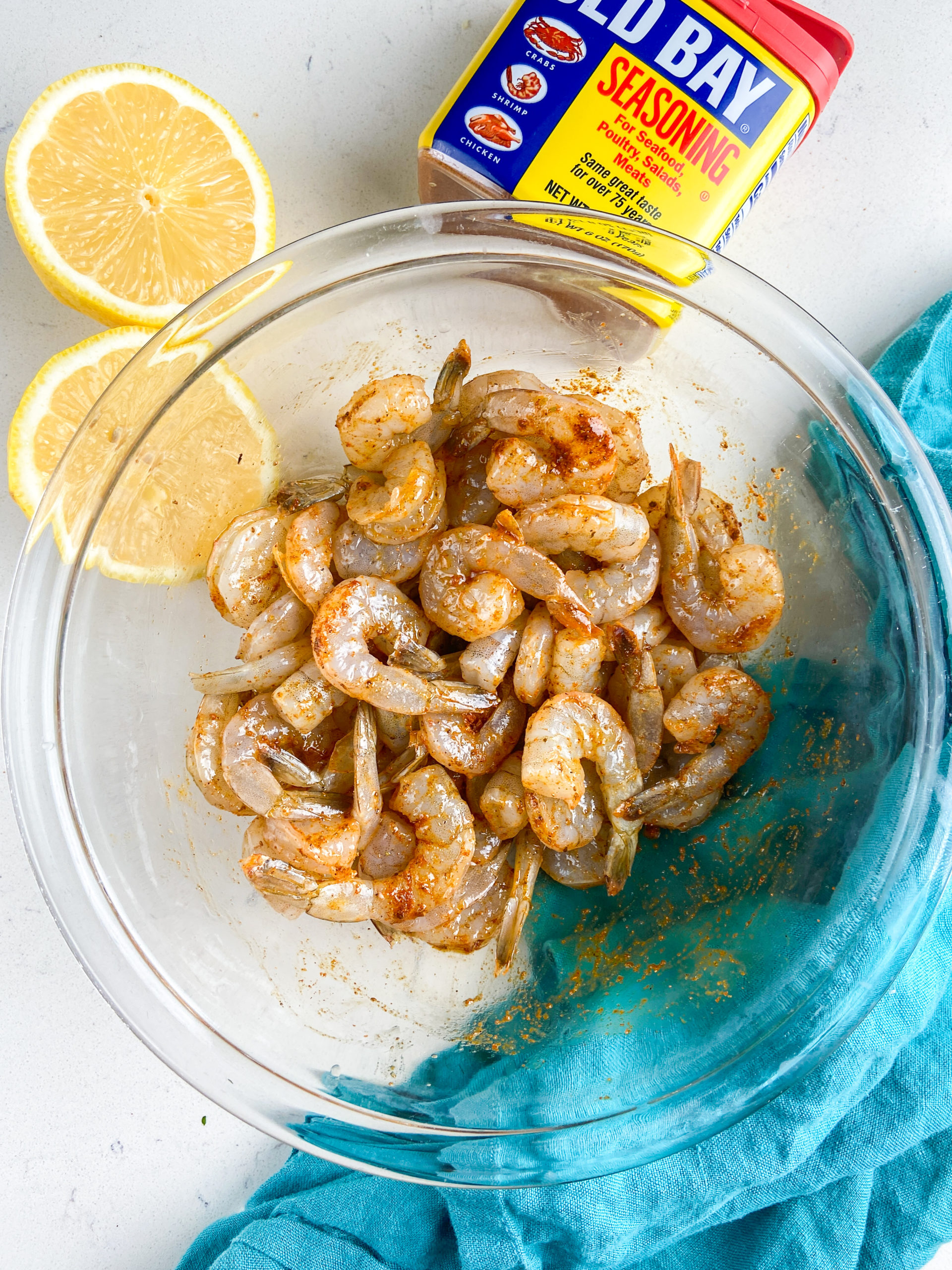 Overhead photo of shrimp mixed with old bay seasoning and olive oil.