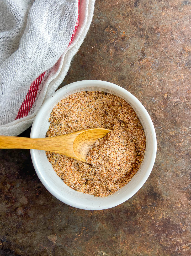 All purpose seasoning blend in a white bowl on cookie sheet with white and red stripped towel.