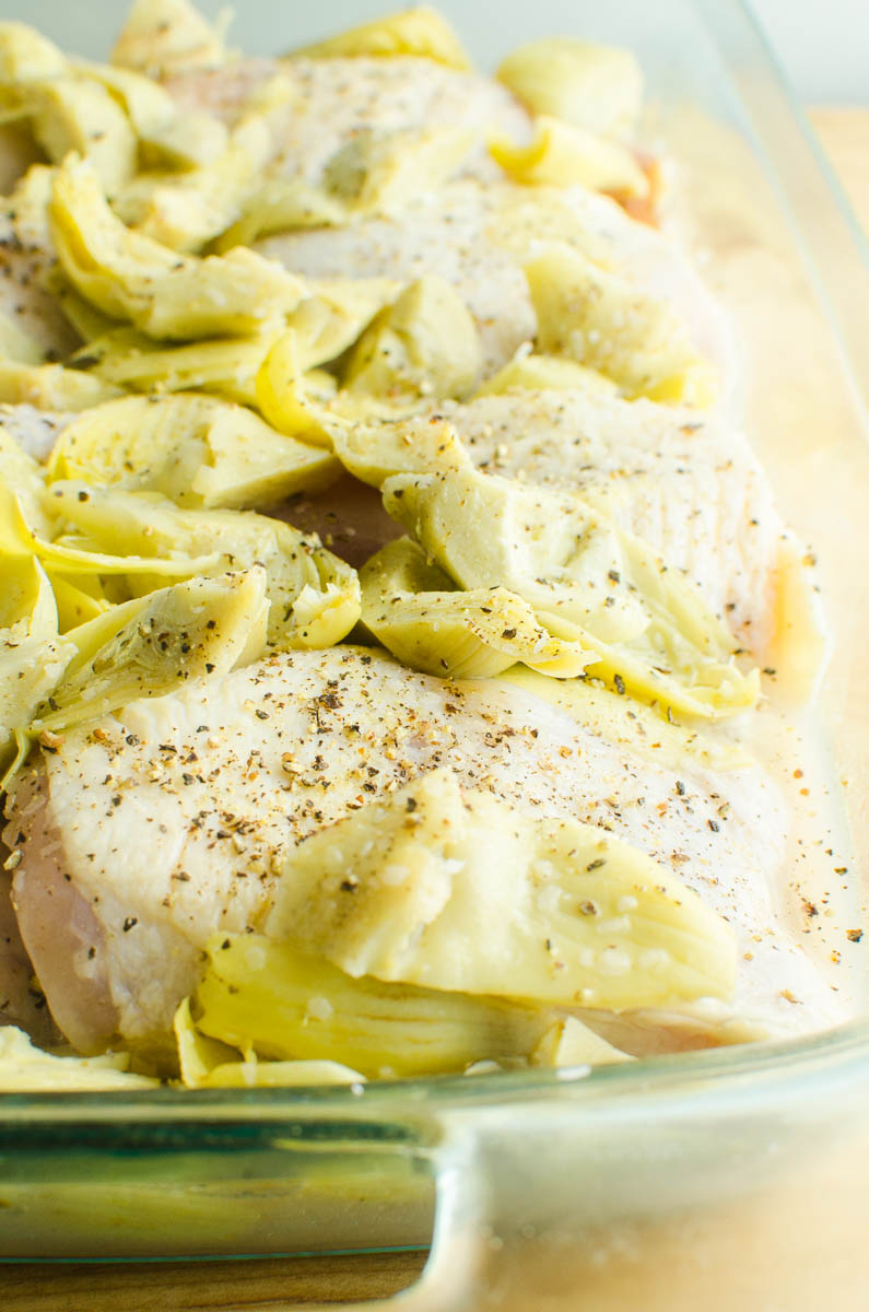 Raw chicken thighs with salt, pepper and artichoke hearts.