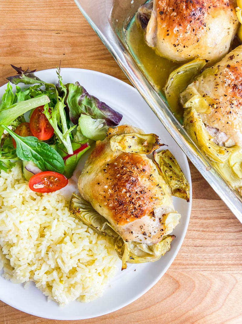 Artichoke Chicken on a white plate with salad and rice.