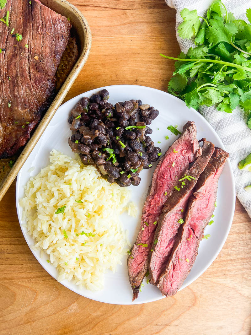 Overhead photo of sliced carne asada on a white plate with beans and rice.