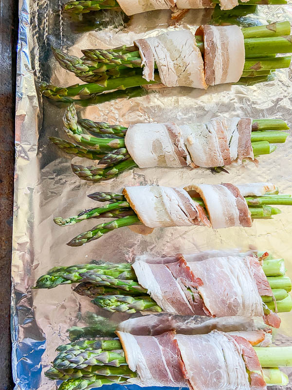 Bacon wrapped asparagus on aluminum foil lined baking sheet.