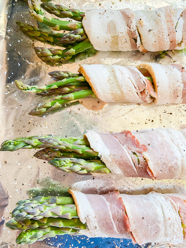 Bacon wrapped asparagus sprinkled with salt and pepper on an aluminum foil lined baking sheet.