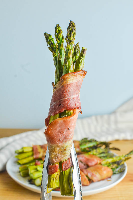 Asparagus wrapped bacon bundle held in kitchen tongs with blue background.