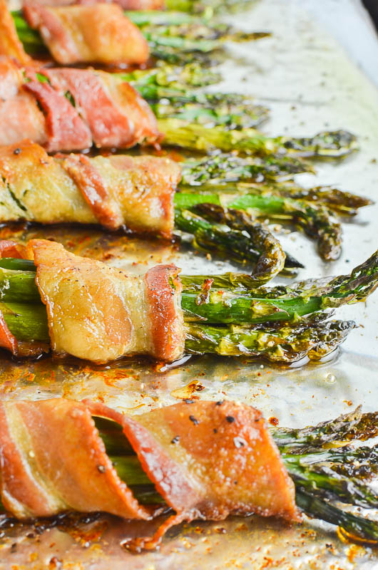 Asparagus wrapped in bacon on aluminum foil. Side angle shot.