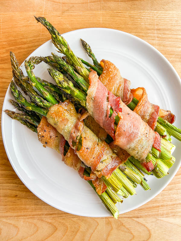 Overhead photo of bacon wrapped asparagus on a white plate and wooden cutting board.