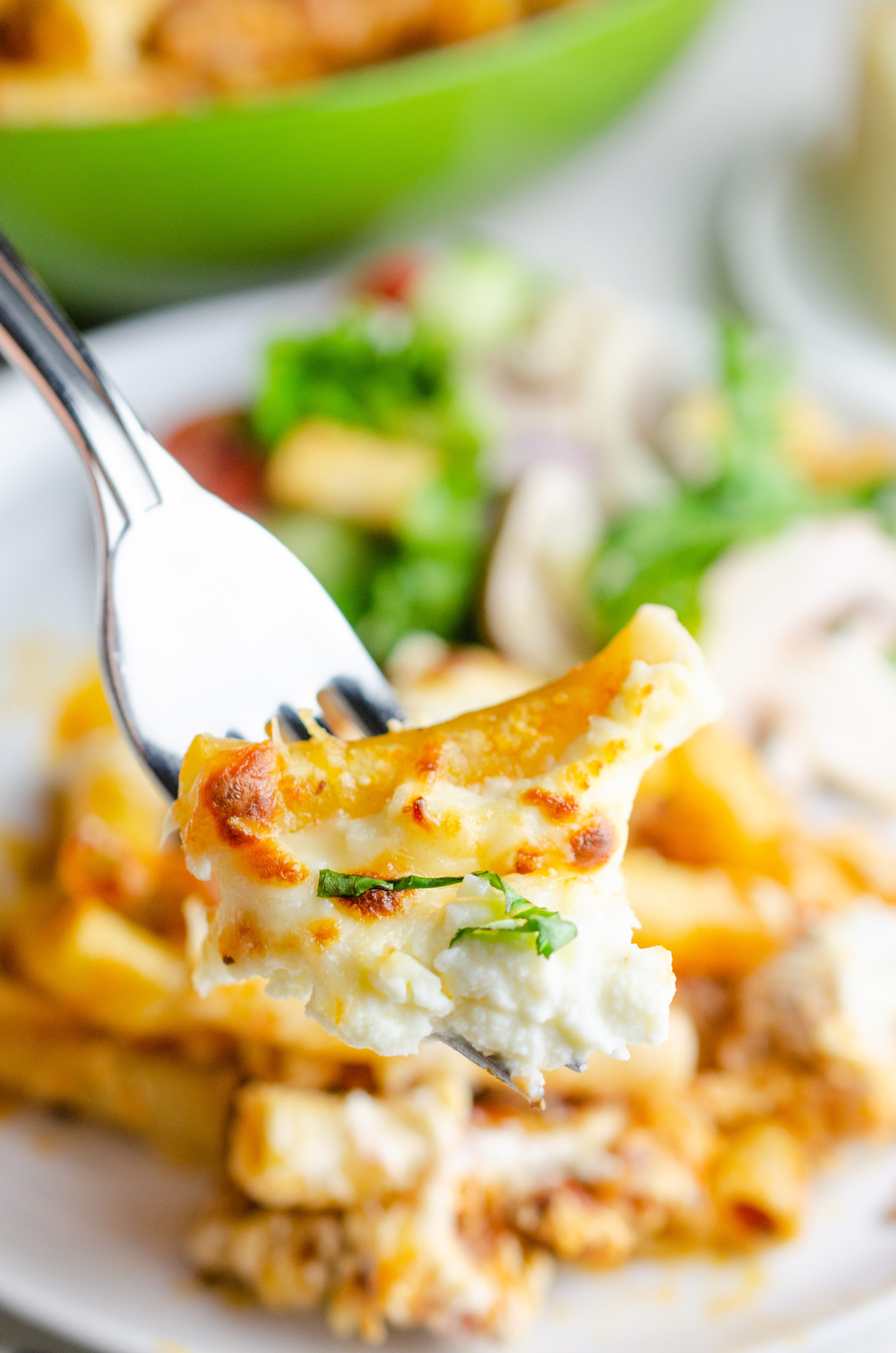 Cooked pasta with cheese on a fork.