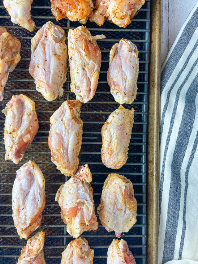 Chicken wings on top of cooling rack on baking sheet.