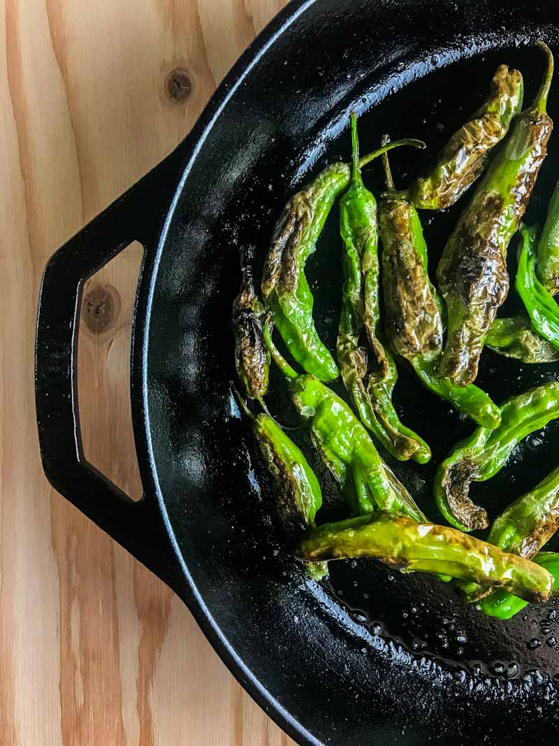 Blistered shishito peppers are pan fried until crispy and served with a sriracha cream sauce. A quick and easy appetizer for pepper lovers!