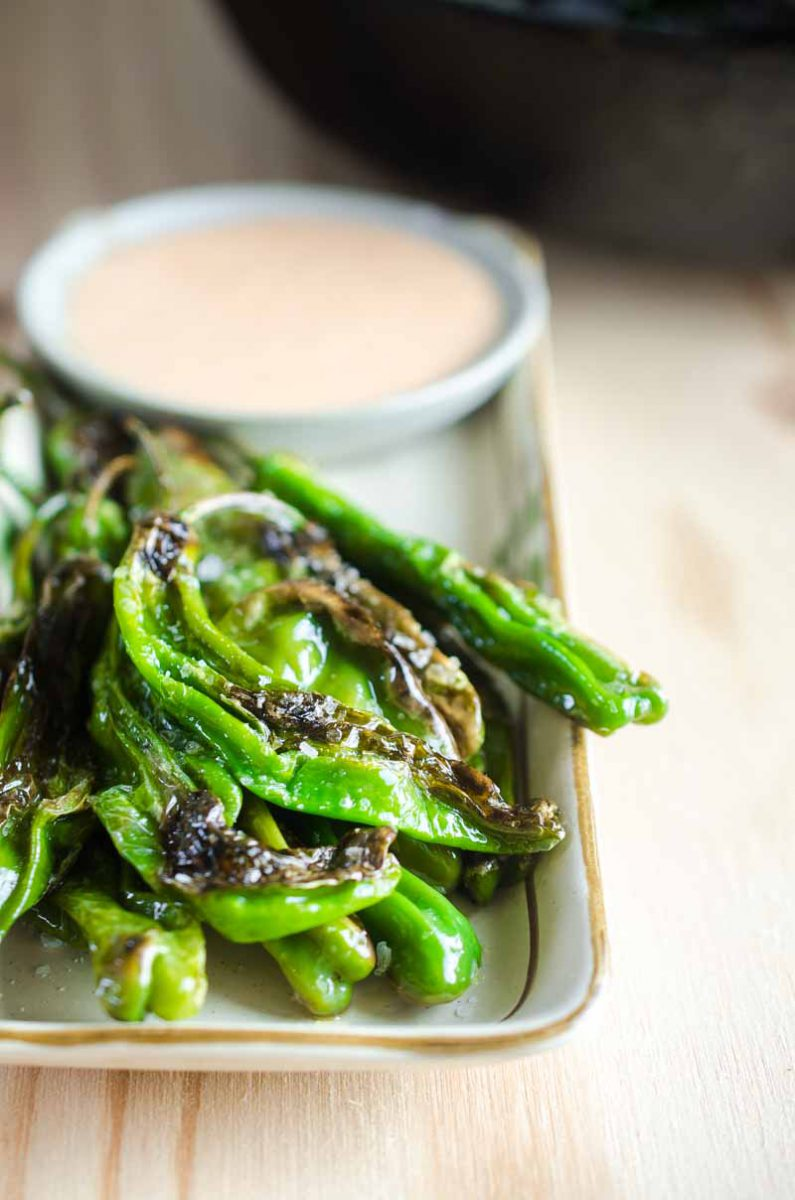 Blistered shishito peppers are pan fried until crispy and served with a sriracha cream sauce. A quick and easy appetizer for pepper lovers