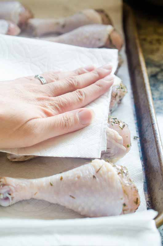Patting dry brined chicken with a paper towel.