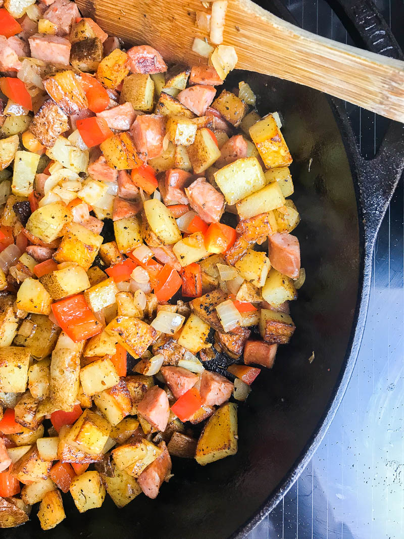 Overhead photo of diced potatoes and vegetables in a skillet.