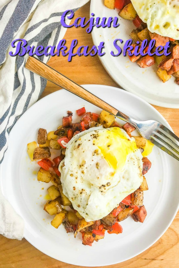Cajun Breakfast Skillet is loaded with potatoes, andouille sausage, onions, bell peppers and cajun seasoning. Then topped with a perfectly fried egg. It's an easy, hearty way to start your day!  #breakfast #cajun #andouillesausage #eggs #brunch