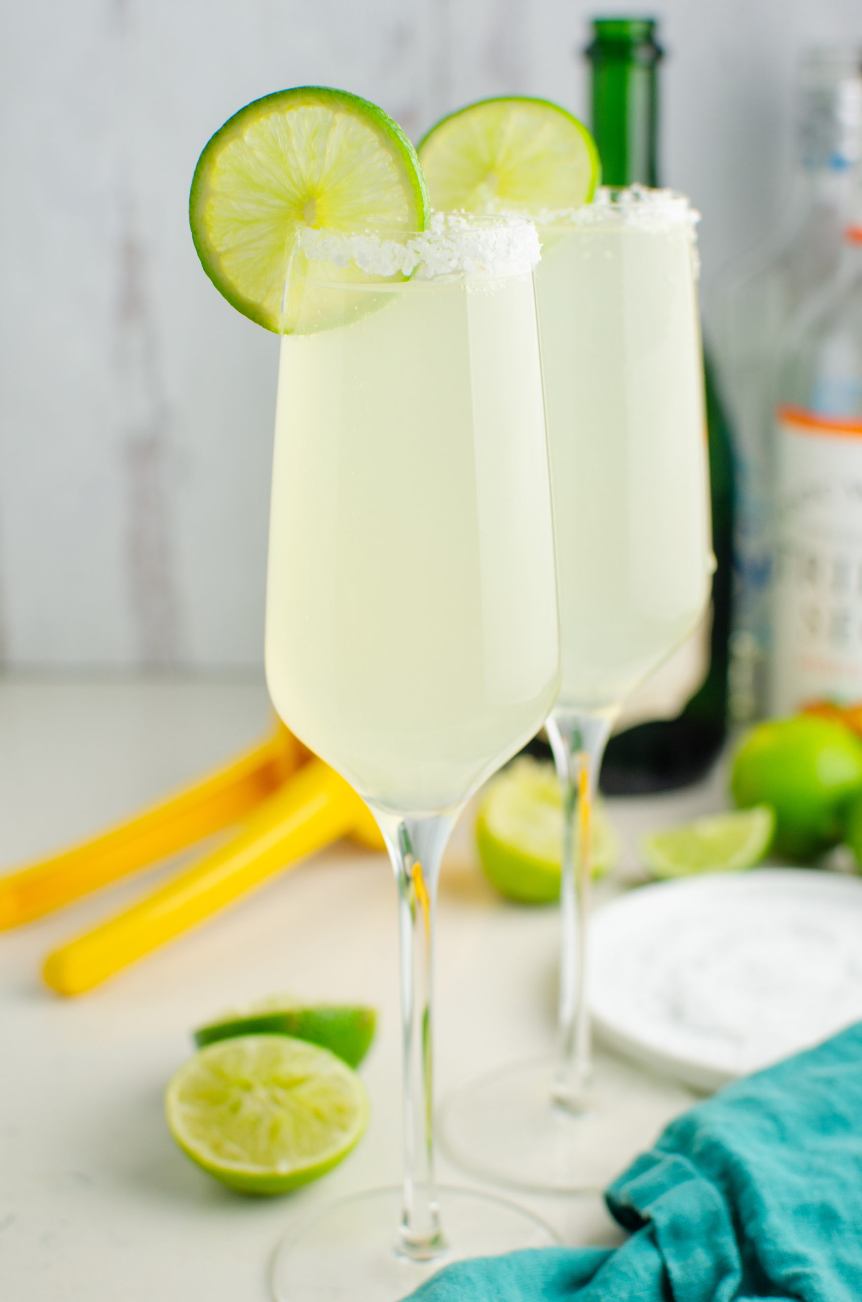 Two champagne margaritas garnished with lime.