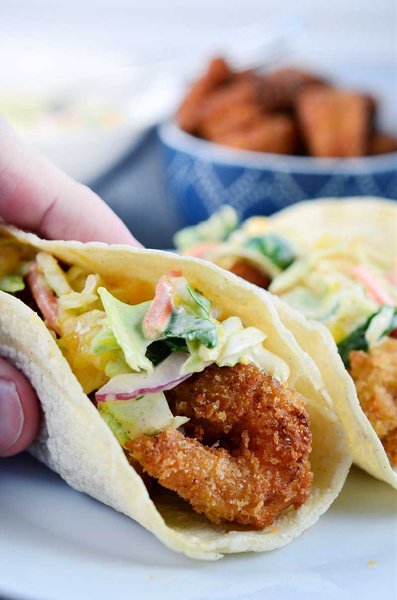 If you are looking for the perfect fried shrimp tacos these are it! These crispy shrimp tacos are loaded with crispy golden fried shrimp and a creamy mango slaw.