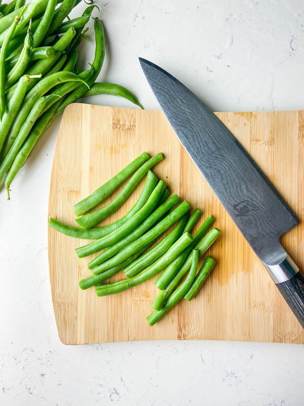 Green beans on a wooden cutting board with a knife.