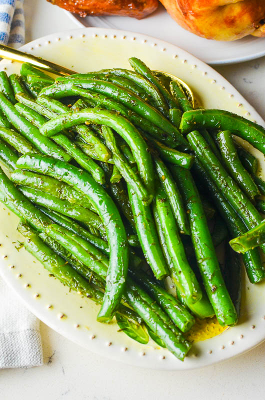 Dill green beans on a white oval dish.
