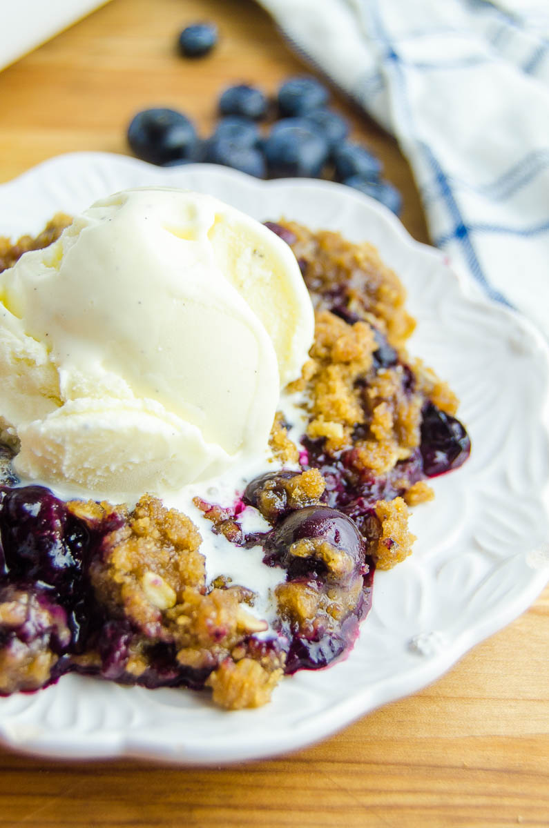 Side angle photo of blueberry crisp with ice cream on top.