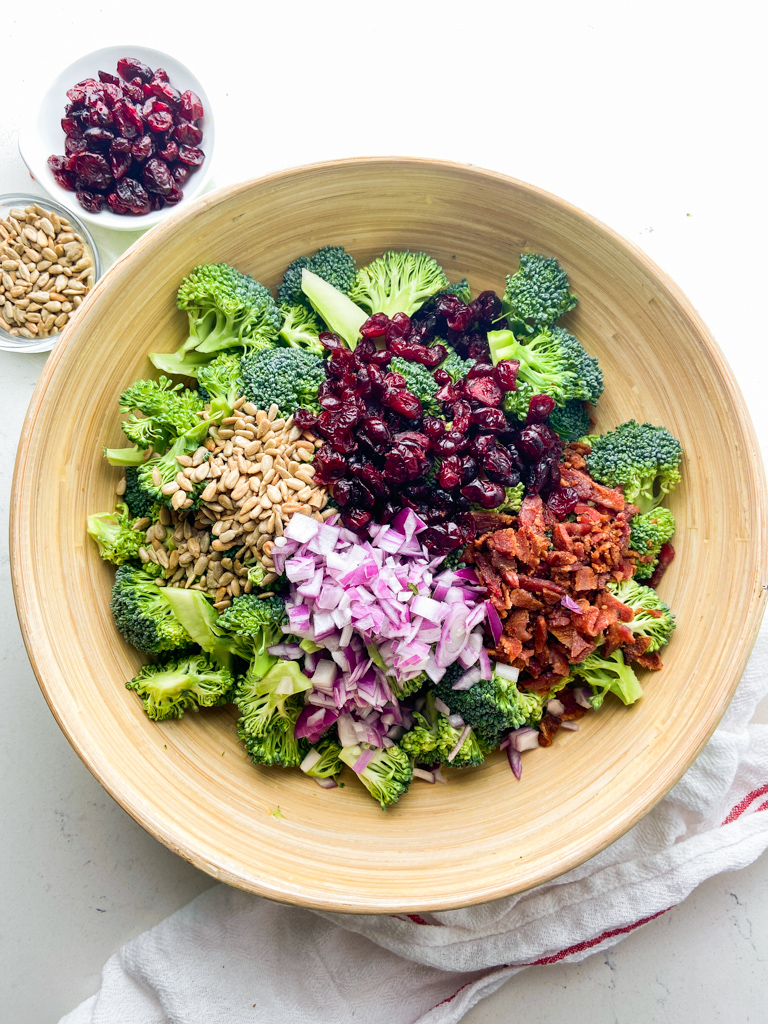 Broccoli salad ingredients in a wooden bowl.
