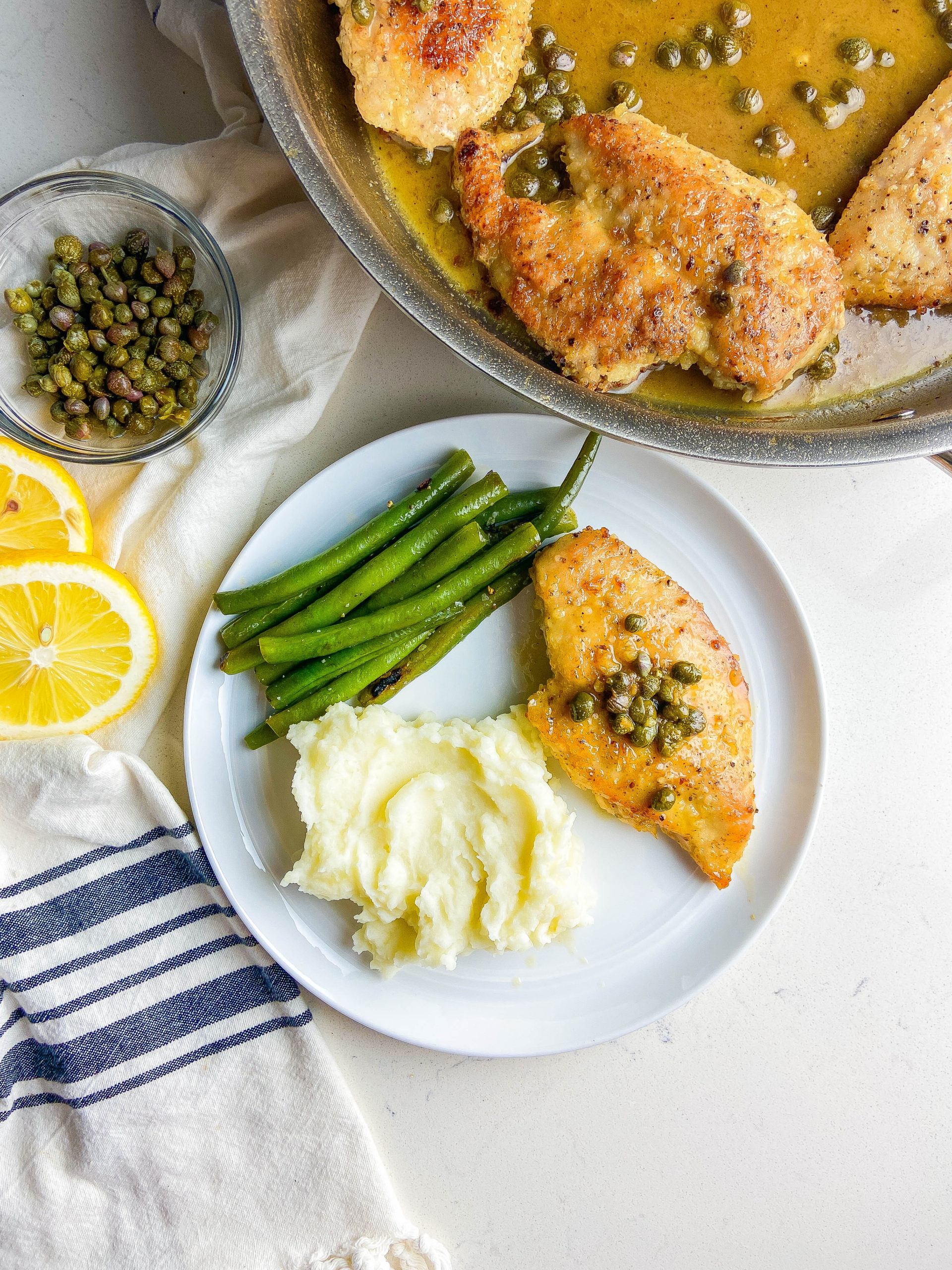 Overhead photo of chicken piccata on a plate with mashed potatoes and green beans.