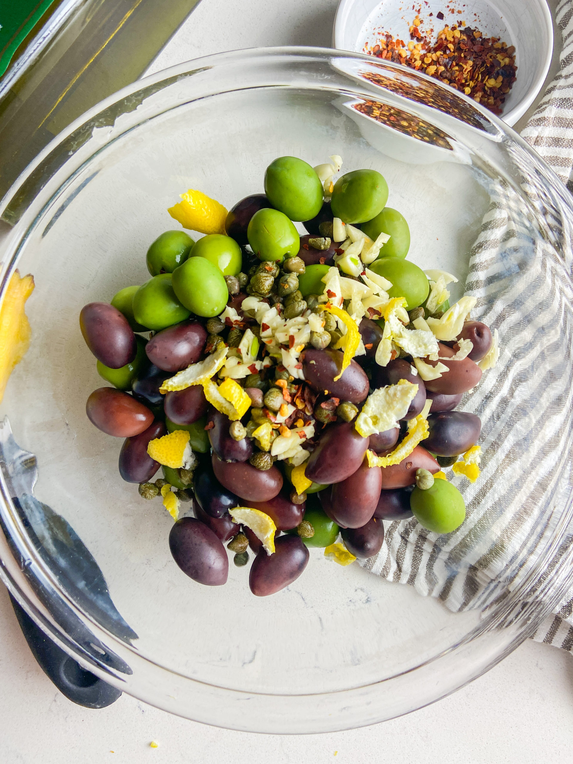 All ingredients for marinated olives in a clear bowl.