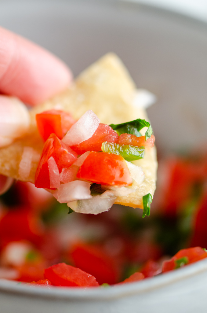 Close up of chip with pico de gallo on it.