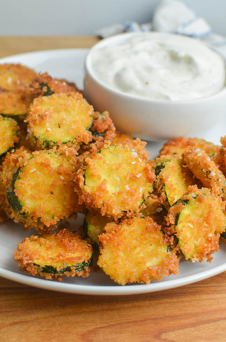 A white plate with fried zucchini and ranch dip on a wooden cutting board.