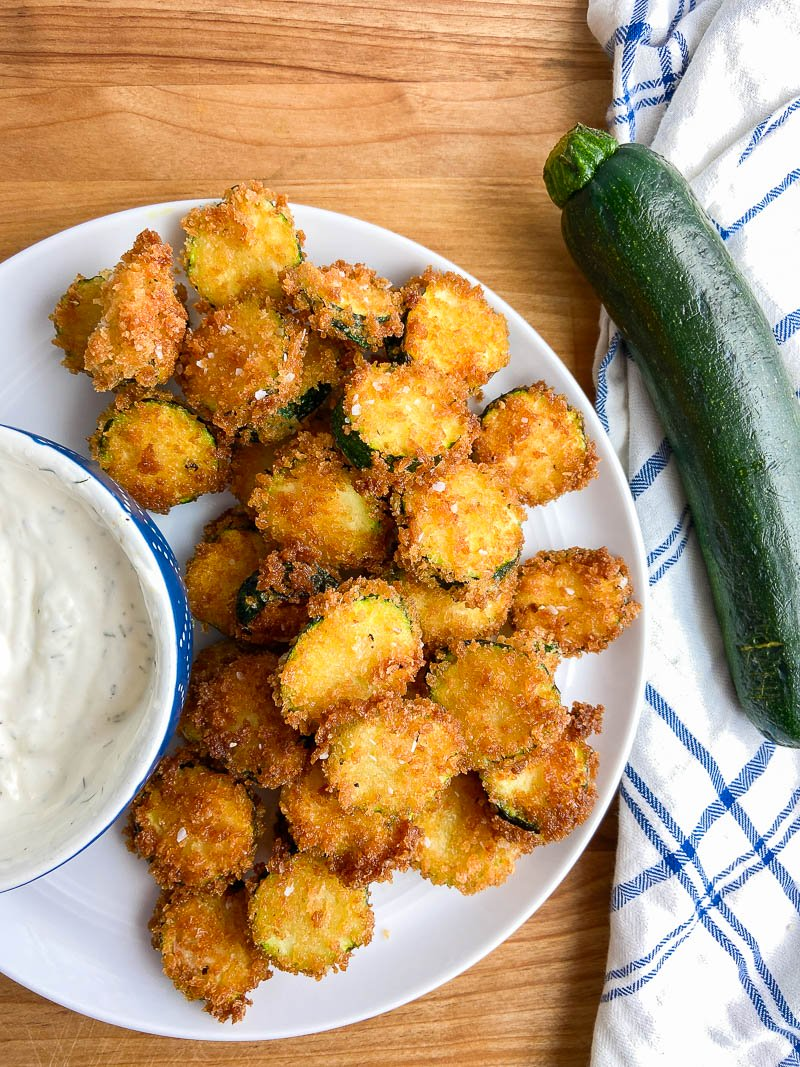 Overhead photo of fried zucchini on a white plate with uncut zucchini on a white and blue towel.