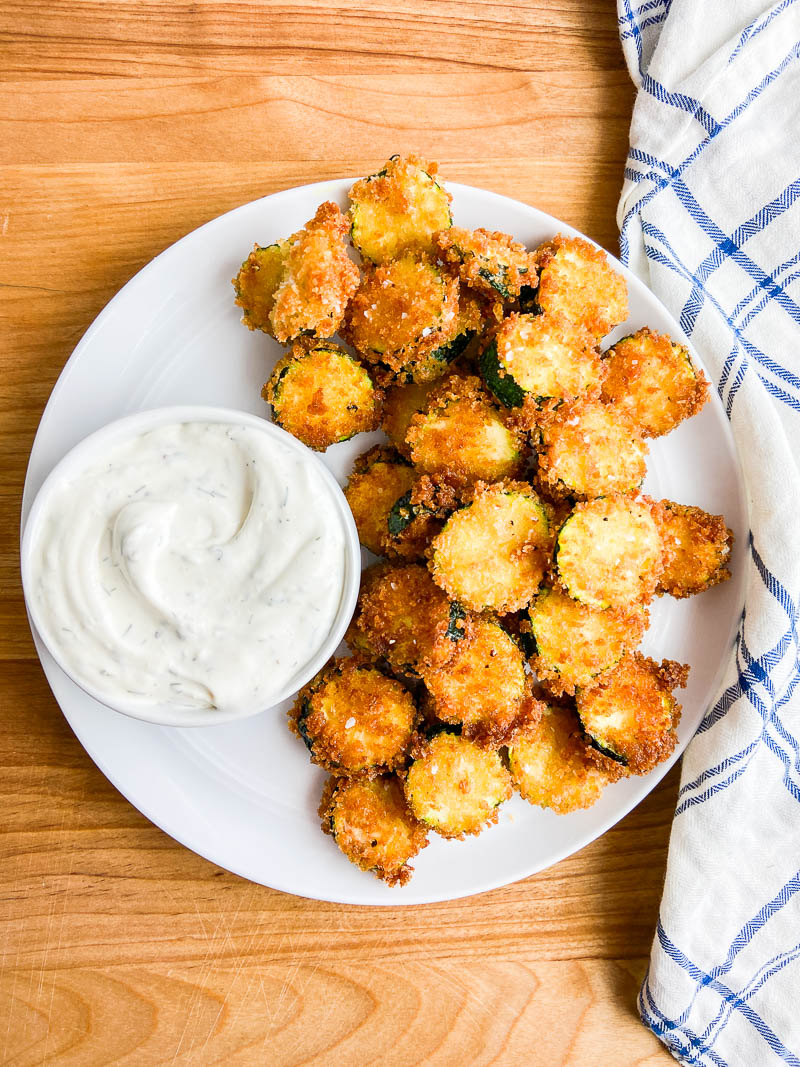 Fried Zucchini on a white plate with ranch dip. A wooden cutting board and a blue and white napkin.