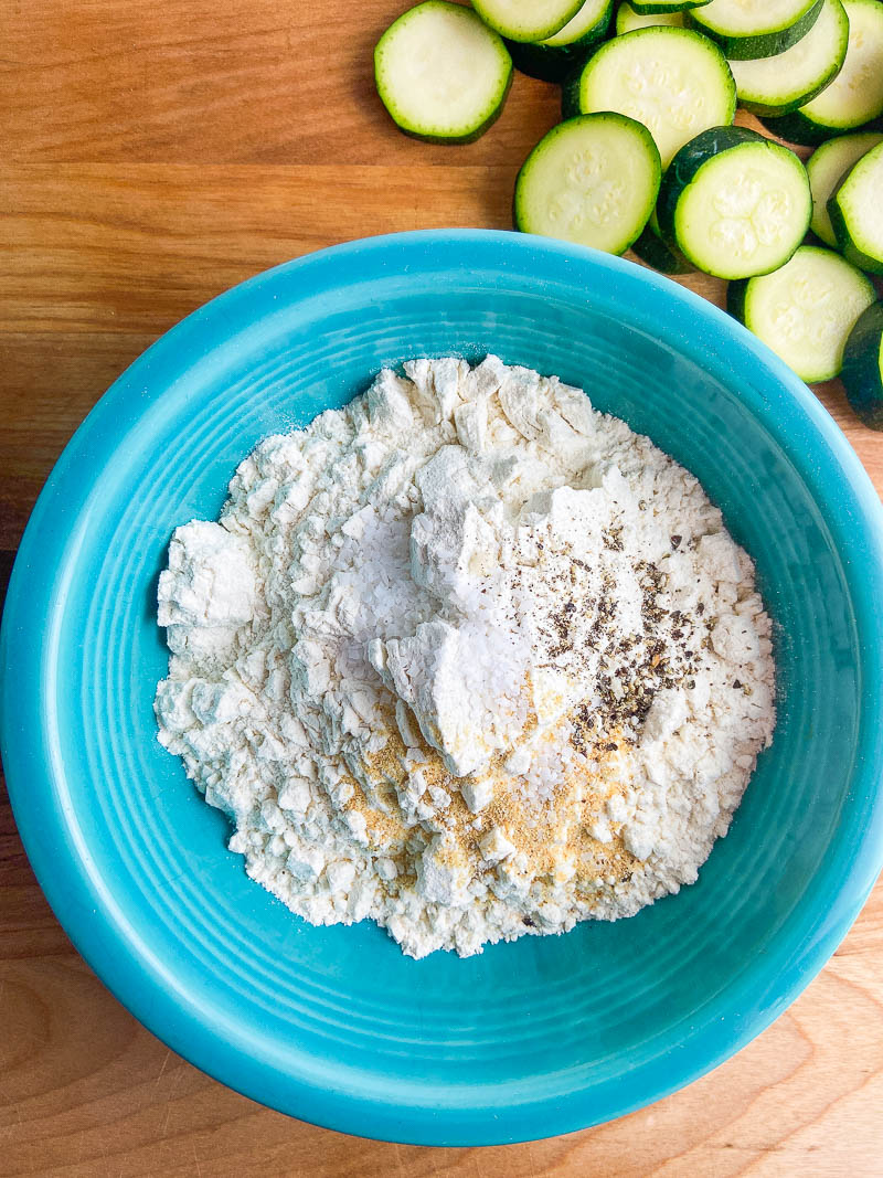 Seasoned flour in a teal bowl with zucchini on a wooden cutting board.