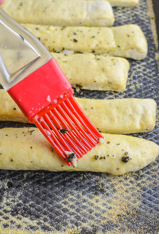 Brushing garlic butter on breadsticks with a red pastry brush.