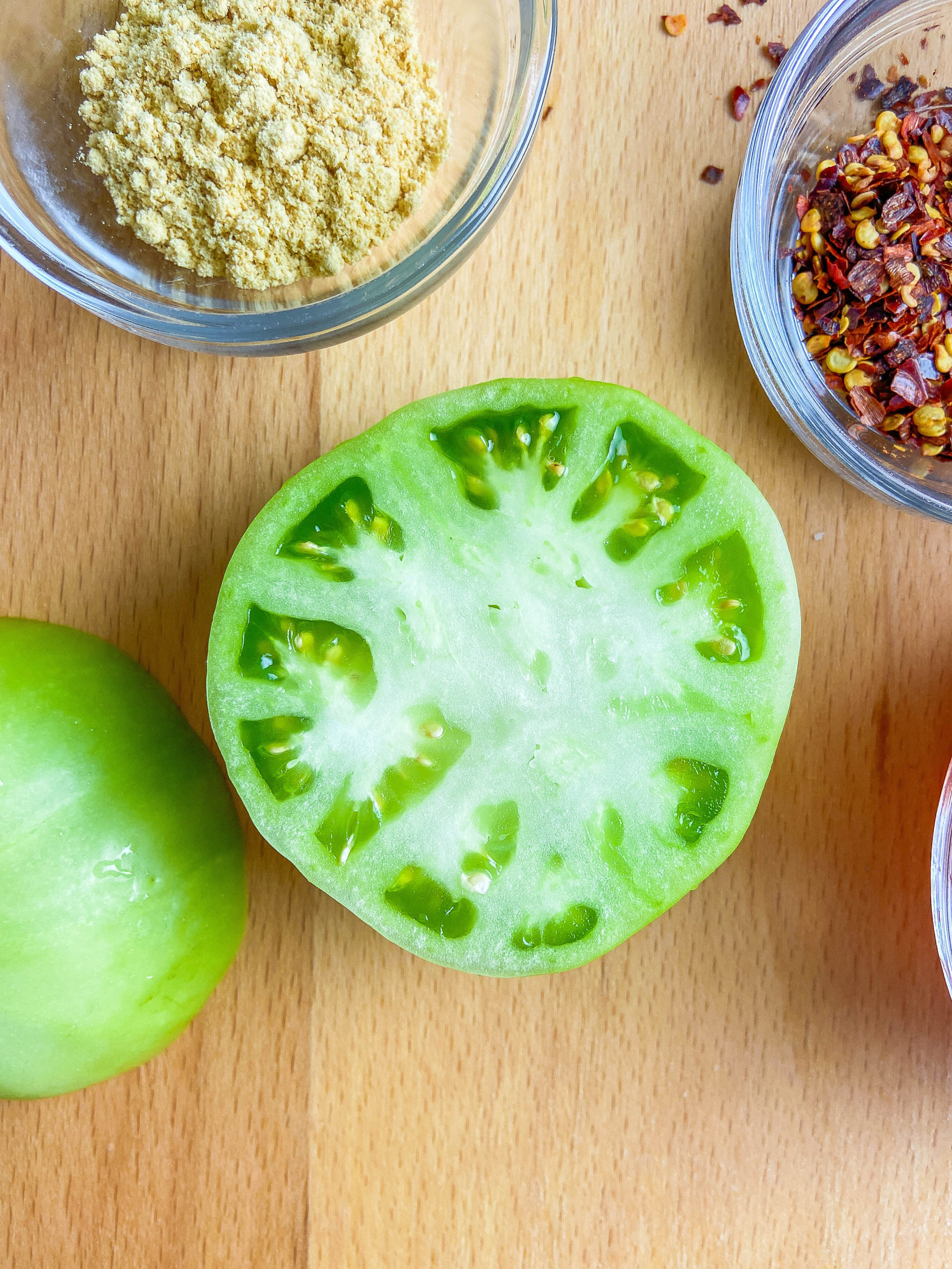 Halved green tomato on a wooden cutting board